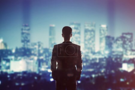 Photo for Man in suit looking to night city - Royalty Free Image