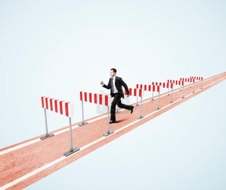 Photo pour Homme d'affaires sautant par-dessus la barrière sur un fond bleu - image libre de droit