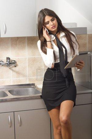 Photo pour Jeune femme dans la cuisine de travail, parler au téléphone . - image libre de droit