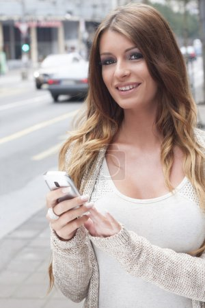 Young Woman with cell phone walking