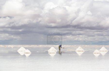Photo pour Travailleur effectuant la récolte du sel sur le lac salé Salar de Uyuni, Bolivie - image libre de droit