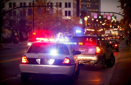 Photo for A police officer pulls over a driver for a traffic violation in a downtown city - Royalty Free Image