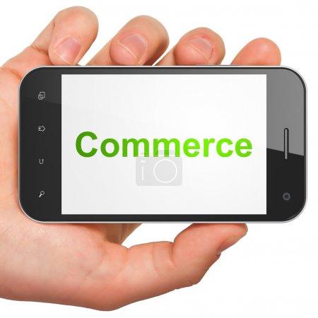 Photo pour Main tenant le smartphone avec commerce de mot sur l'écran. générique mobile téléphone intelligent en main sur fond blanc. - image libre de droit