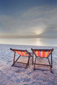 Wood chairs bed and umbrella on sand beach at sun set time
