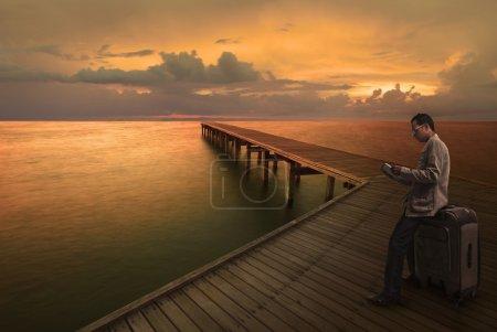 Photo pour Homme lisant un guide sur le pont en bois avant de se rendre à un autre endroit - image libre de droit