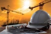 Sicherheits-Helm und Architekt Pland auf Holztisch mit Sonnenuntergang scen