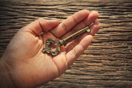 Photo pour Résumé de fichier de clé métallique sur la main gauche contre la texture de fond bois écorce avec espace copie - image libre de droit