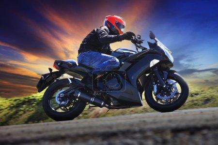 Photo pour Jeune homme motocyclette sur la courbe de la route de campagne asphalte contre l'utilisation de ciel sombre pour les activités sportives, loisirs masculine et thème de voyage - image libre de droit