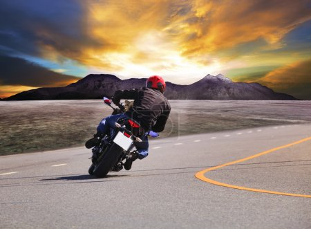 Rear view of young man riding motorcycle in asphalt road curve w