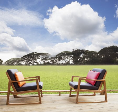 Relax chairs on wood terrace with grass field and beautiful sky