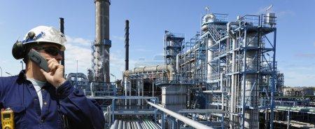 Photo pour Travailleur pétrolier et gazier avec raffinerie géante en arrière-plan, vue panoramique - image libre de droit