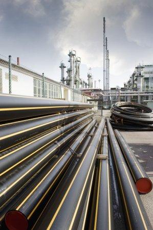 Photo pour Pipelines au sol devant une raffinerie de pétrole et de gaz - image libre de droit