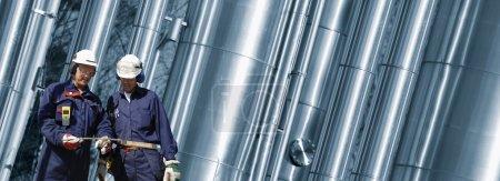 Photo pour Travailleurs du pétrole et du gaz avec construction de pipelines géants en arrière-plan, vue panoramique - image libre de droit
