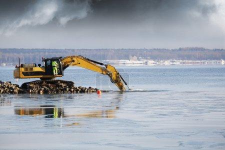Photo pour Gros bulldozer dragage des roches dans la mer, l'industrie de l'excavation, la neige et la glace - image libre de droit