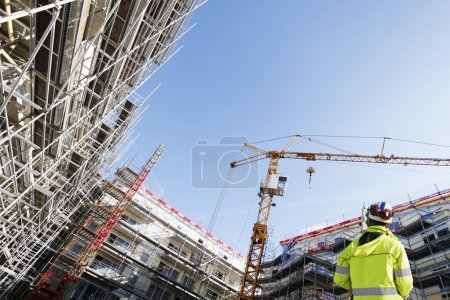Photo for Surveyor, engineer with measuring instrument, working inside construction-site, superwide perspective. small red text is just name of planks. - Royalty Free Image