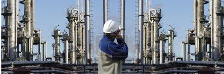 Photo pour Travailleur pétrolier devant une grande industrie pétrolière et gazière panoramique, des pipelines et des tours - image libre de droit