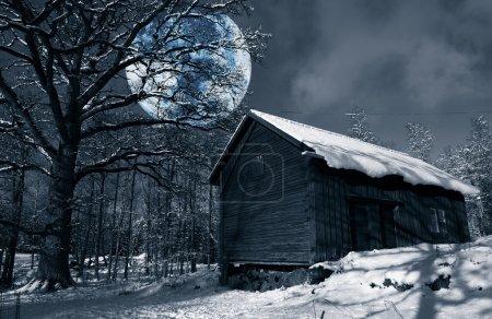 Photo pour Grande pleine lune surréaliste planant au-dessus de la vieille grange rurale, paysage hivernal de Suède - image libre de droit