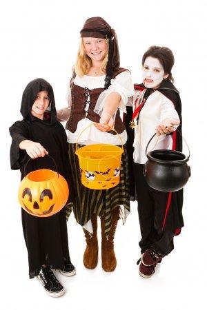 Foto de Tres niños de varias edades vestidas para halloween. cuerpo completo aislado en blanco. - Imagen libre de derechos