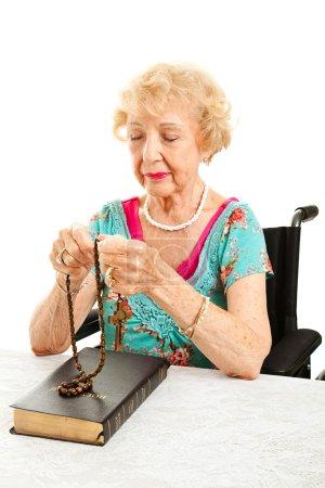 Photo pour Grand-mère catholique âgée en fauteuil roulant en prière avec le chapelet de perles. fond blanc. - image libre de droit