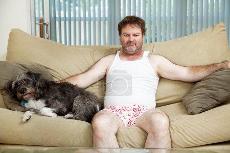 Photo pour Homme sans emploi découragé à la maison dans ses sous-vêtements, assis sur le canapé avec son chien. - image libre de droit