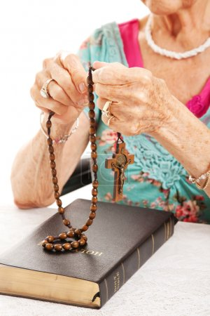 Photo for Closeup of senior woman's hands as she says the rosary. - Royalty Free Image