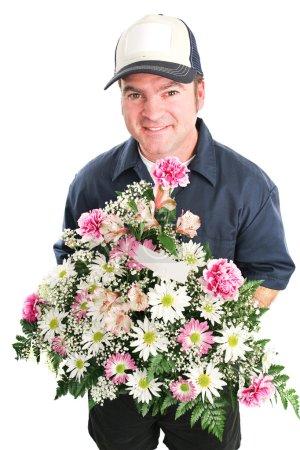 Photo pour Livreur offre un bouquet de fleurs pour la journée de la mère, anniversaire ou autre occasion spéciale. isolé sur blanc. - image libre de droit