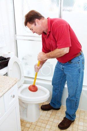 Man in his bathroom unclogging a toilet with a plu...