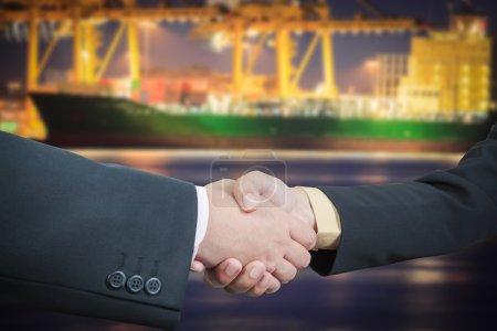 Businessman handshake with ship transportation logistic backgrou