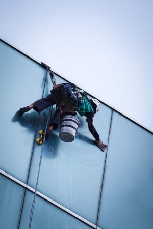 worker cleaning windows service on high rise building