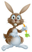 Cute cartoon bunny rabbit or Easter bunny holding a carrot and looking at viewer