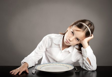 Photo for Little girl sitting at table in front of an empty dish - Royalty Free Image