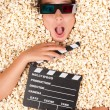 Young girl buried in popcorn with movie clapper bo...