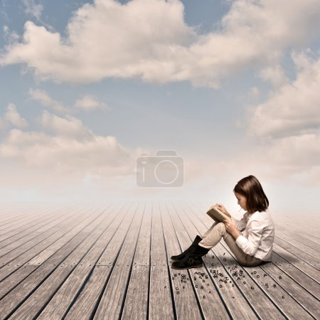 Photo for Little girl reading a book on a wharf - Royalty Free Image