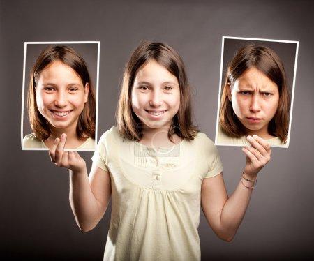 Foto de Retrato de joven sosteniendo dos fotos de ella con expresiones felices y tristes - Imagen libre de derechos