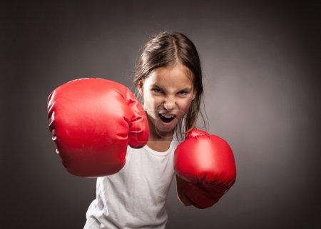 Photo pour Petite fille portant des gants de boxe rouge - image libre de droit