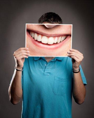 Photo pour Jeune homme tenant une photo d'une bouche souriante - image libre de droit