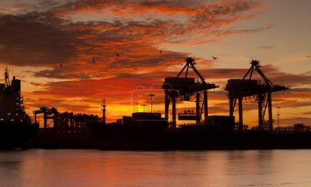 Photo pour Conteneur cargo cargo avec pont-grue de travail dans le chantier naval au crépuscule pour l'importation logistique contexte d'exportation - image libre de droit