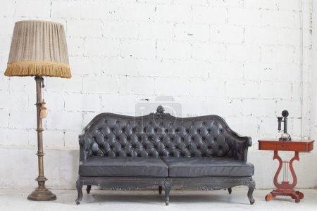 Photo pour Canapé antigue en cuir noir dans une chambre blanche . - image libre de droit