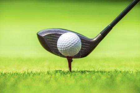 Golf ball behind driver at driving range