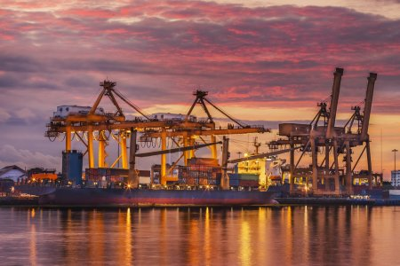 Photo for Container Cargo freight ship with working crane bridge in shipyard at dusk for Logistic Import Export background - Royalty Free Image