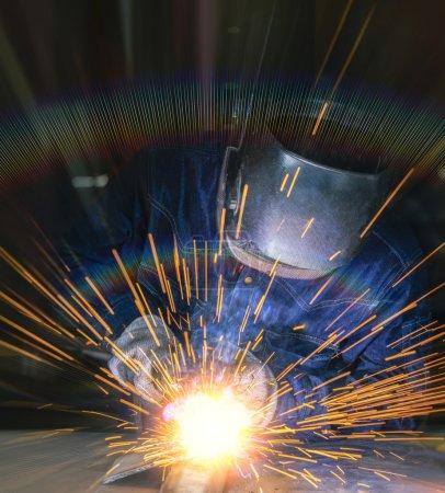 Photo pour Travailleur soudant la partie en acier manuellement - image libre de droit