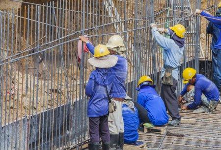 Photo pour Constructeurs authentiques travaillant ensemble pour positionner des cadres de coffrage en béton en place - image libre de droit