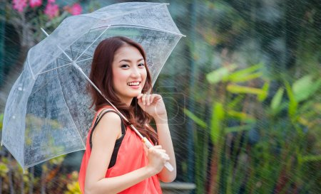 Photo pour Jeune femme thaïlandaise debout avec sous le parapluie sous la pluie - image libre de droit