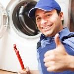 Portrait of a technician repairing a washing machi...