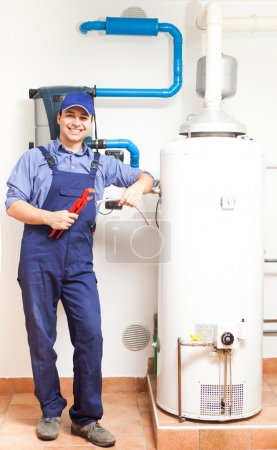 Photo for Smiling technician repairing an hot-water heater - Royalty Free Image