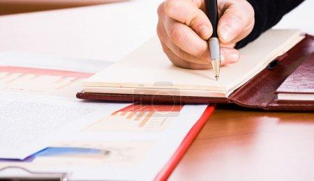 Photo pour Un homme d'affaires écrit sur un carnet - image libre de droit