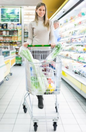 Photo for Beautiful woman shopping in a supermarket - Royalty Free Image