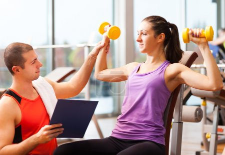 Photo for Personal trainer showing an exercise to a woman - Royalty Free Image