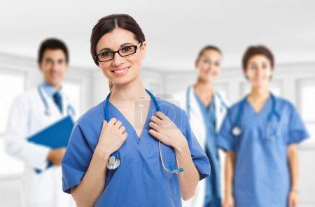 Photo pour Portrait d'une infirmière souriante devant son équipe médicale - image libre de droit