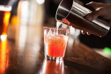 Photo for Bartender serving a cocktail from a shaker - Royalty Free Image